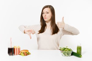 Woman shows thumbs up down with green detox smoothies, salad in glass bowl, cucumber burger cola in bottle isolated on white background. Proper nutrition, healthy lifestyle, fast food, choice concept.