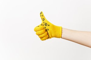 Close up of female hand in building yellow gloves showing thumb up isolated on white background. Accessories for renovation apartment room. Repair home concept. Copy space for advertisement.