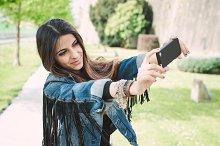 Woman taking a selfie in a park