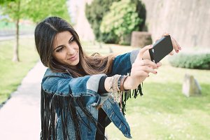 Woman taking a selfie in a park