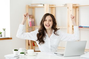 Successful business woman with arms up sitting in modern office.