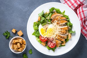 Caesar salad with chicken breast and tomatoes.