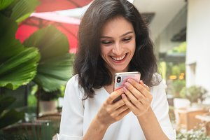 Happy woman with smartphone in a restaurant terrace with an unfocused background