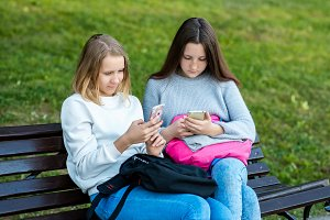 The best friends in the summer in park fresh air. Girls schoolgirl on a bench holds smart phones. It is corresponded in social networks.