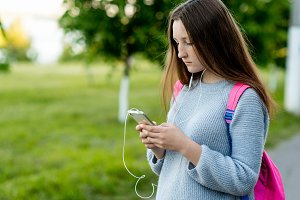 Little girl schoolgirl brunette. After school at school. Behind back is a pink backpack. In hands holds a smartphone. Listens music headphones watching movie. Writes message to parents friends.