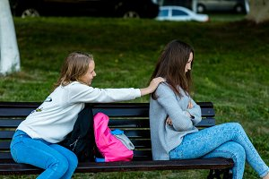 Two girlfriends in summer on the bench. Offended each other. Friends quarreled. Nigativa among girls. The problem is in the relationship. Dissatisfaction with each other.