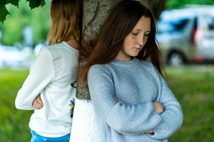 Two girlfriends in the summer in a park in nature. Offended each other. Friends quarreled. Negative among the girls. Problems in the relationship. Dissatisfaction with each other. Stand near a tree.