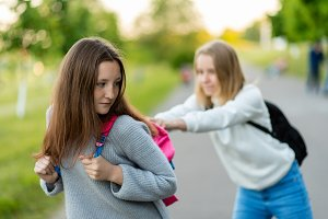 Girls are schoolgirls. Summer in nature. Taking each other's bags away. Fight after the lessons. Poor upbringing of adolescents. Problem children.