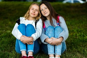 Two teenage girl. Summer in nature. They are sitting on grass. Communicate with each other. To pose on the camera. Best friends. Privacy from adults.