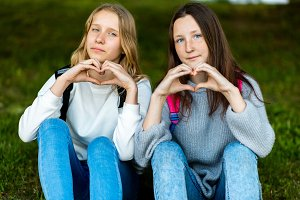 Beautiful two teenage girls. Summer in nature. After school at school. They are sitting on grass. Gestures of hands show heart. Beautiful eyes and long hair. Emotional Tenderness. Love to parents.