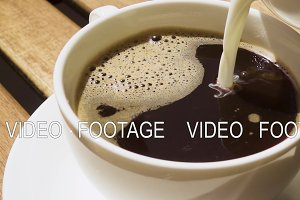 Milk from a milkman pour into coffee slow motion