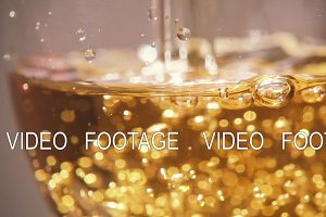Slow motion in a glass to pour a yellow drink with bubbles