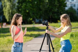 Little girls teenager. Summer in nature. They broadcast live on the camera. Record vlog and blog subscribers. Record video lesson for Internet. Use camera with tripod.