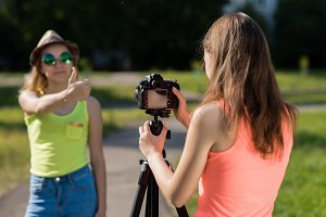 Two girl friends. Summer in nature. Shows the gesture of the thumb up. A bright sunny day. Record vlog and blog subscribers. Record video lesson for Internet. Use camera with tripod.