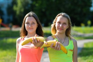 Two girl friends. Summer in nature. Happy extends a hand in the hands of banana. Healthy lifestyle. Proper nutrition of children. Useful fruit for school children.