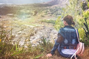 Young woman sitting on a rock with backpack and looking to the horizon. Bali island. Volcano Batur.
