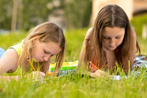 Two girls are students. Young Teens. Do the lessons write in a notebook in the summer on grass. Camping. Fills out notes draws notebooks. Perform tasks for the school.