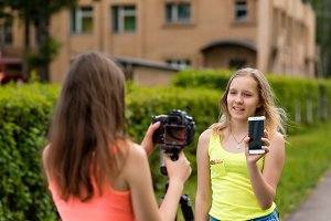 Two girls are bloggers. Young journalists. Describes advantages of phone. Make a broadcast on the Internet. Record vlog and blog subscribers. Record video lesson for Internet. Use camera with tripod.