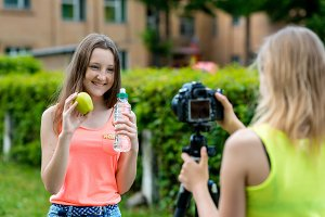 Two girls in the summer in nature. They talk about healthy eating. In the hands of an apple a bottle of water. Smiles happily. Record vlog and blog subscribers. Record video lesson for Internet.