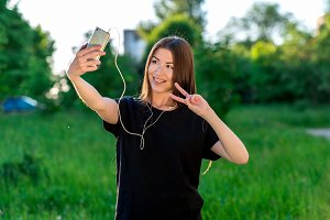 Happy Asian girl smiling at the camera. To call by video call. Speaks on the phone listening to music. Hand gestures. Hello. Summer in field on a green meadow. He speaks in social networks.