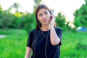 Beautiful brunette girl listening to music on headphones in summer in outdoor park. Emotional looking up dreams to fantasize. Smiling positive thoughts about good