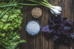overhead flat lay of herbs salt and corn on wooden table with basil leafs