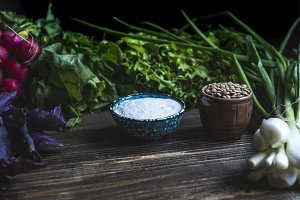 close up assortie of herb, salt cup and lentils on dark background