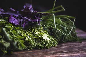 close up mix of herbs on wooden table in dark background