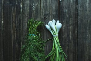 close up bunches of fresh raw green onion and dill flat lay