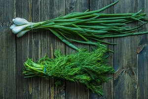 bunch of green onion and dill on a wooden surface
