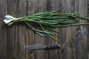 green onion bunch with knife overhead on a wooden table