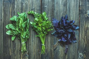 basil parsley sorrel herbs mix flat lay overhead on a wooden surface