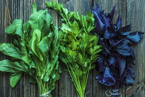 three bunch of fresh raw herbs on wooden table