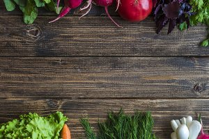 flat lay of fresh herbs and vegetables on a wooden surface