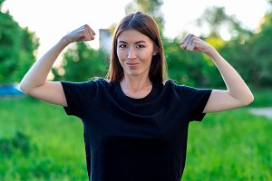 The brunette girl smiles happily. Summer in field on a green meadow. Hands showing biceps. Emotions are jokes female power.