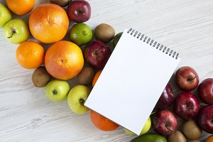 Set of raw fruits with notebook