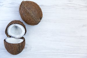 Coconut with half on white wooden