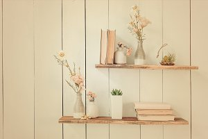 wooden shelves with books and flowers on the wall