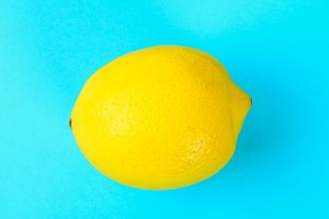 Yellow whole lemon on a pastel blue background.