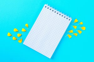 White empty notebook and yellow flower petals on a pastel blue background.
