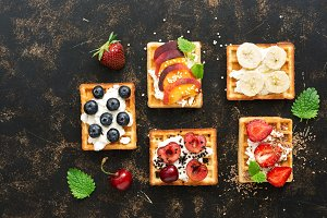 Wafers with cream, fruit and berries on a dark background, top view. The Belgian waffles.