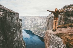 Traveling woman standing on cliff