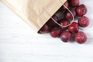 Paper bag of red apples on light