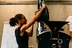 Young businesswoman pouring coffee