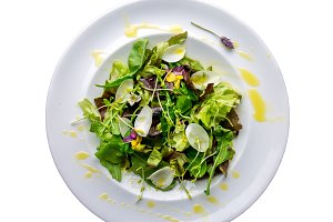 Healthy lettuce arugula salad with edible flowers and microgreens on white plate isolate on white. Top view