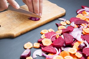 Closeup on man cutting red onion.