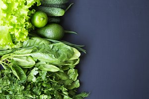 Green vegetables and fruits on dark