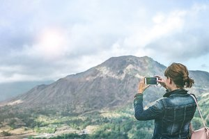 Successful woman hiker taking picture with smartphone at cliff edge on mountain top. Bali island.