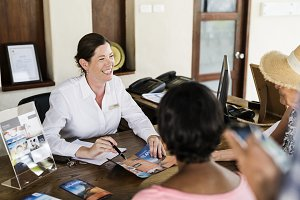 Resort receptionist speaking to a gu