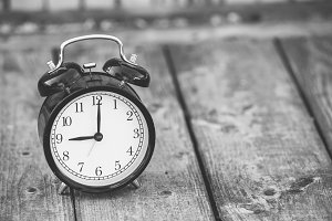 alarm clock showing five o'clock on wooden background, black and white image.